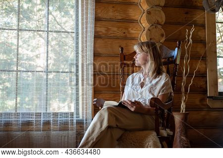 A Beautiful Blonde Woman In Beige Home Clothes Sits In A Cozy Rocking Chair And Reads A Book. Cozy V