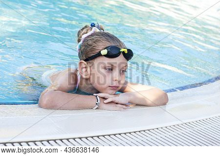 Little Girl In Swimming Goggles Swims In The Pool