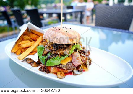 Appetizing Juicy Meat Burgers, Potato Chips And Vegetable In Restaurant. French Fries, Hamburger Or