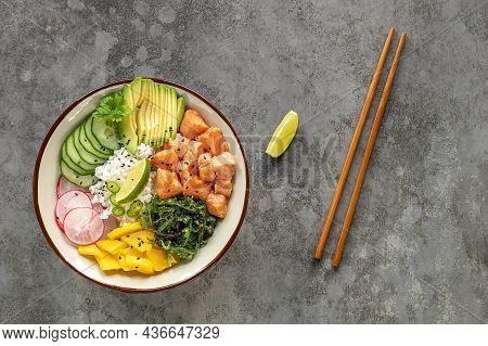 Hawaiian Salmon Fish Poke Bowl With Rice, Mango, Radish, Cucumber, Chukka, Sesame Seeds, And Avocado