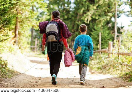 Back Of Mother With Three Kids Walking On Wood Mountains. Family Travel And Hiking With Childrens.