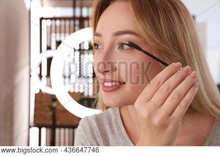 Beautiful Young Woman Applying Mascara Indoors. Using Ring Lamp