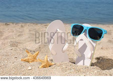 Stylish Flip Flops, Sunglasses And Starfishes On Sandy Beach