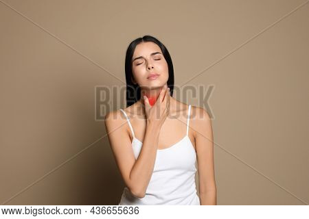 Young Woman Doing Thyroid Self Examination On Beige Background