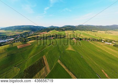 Aerial View Of Agricultural Green Fields And Residential Building In Small European Town Near Mounta