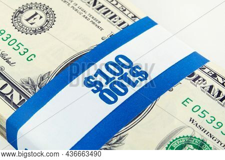 One hundred dollar money bundle with paper currency strap.
