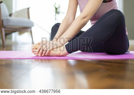 Young Woman Stretching Legs On Exercise Mat In Living Room. Seated Butterfly Leg Stretch Holding Sol