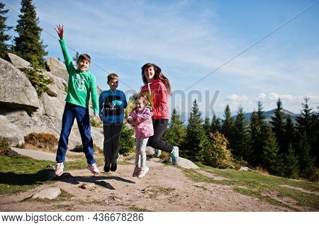 Mother With Four Kids Resting In Mountains. Family Travel And Hiking With Childrens. Jumping Into Th