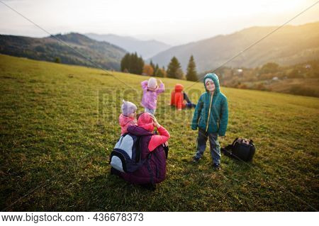 Mother With Four Kids In The Grass Gorgeous Mountain Range In The Horizon.
