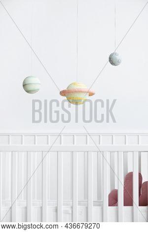 Planetary mobile above a white crib