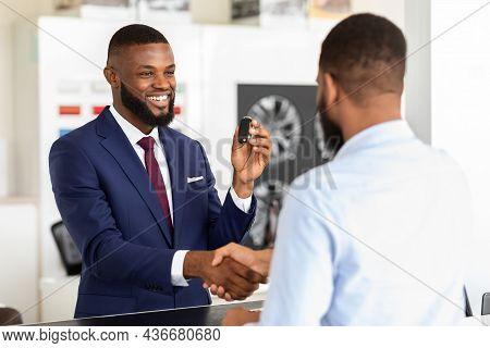 Black Salesman And Male Customer Shaking Hands After Deal In Dealership Center