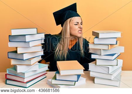 Young caucasian woman wearing graduation ceremony robe sitting on the table suffering of backache, touching back with hand, muscular pain