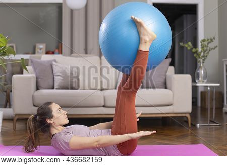 Young Woman Exercising At Home In A Living Room. She Is Exercising With A Fitness Ball
