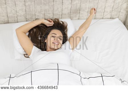 Young Woman Stretching In Bed After Wake Up. Attractive Woman Lying Down In Bedroom At Early Morning