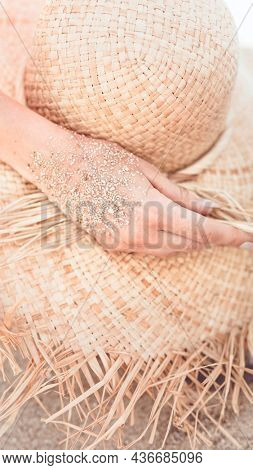 Mobile phone wallpaper, beach sandy hand touch a straw hat warm tone filter