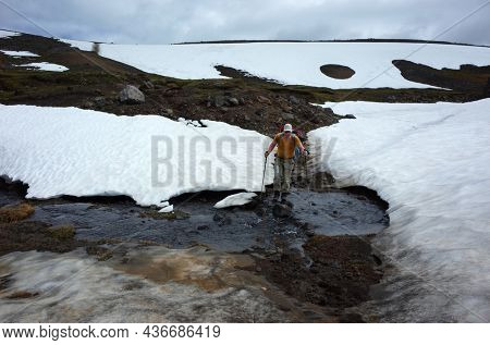 Man is hiking on highlands over melting snow stream in Villarrica national park, Outdoor activity in Patagonia, Chile