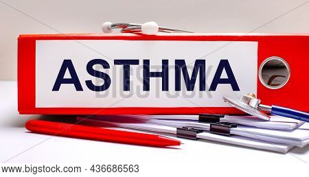 On The Desktop Is A Stethoscope, Documents, A Pen, And A Red File Folder With The Text Asthma. Medic