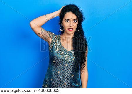 Young woman wearing bindi and traditional kurta dress confuse and wonder about question. uncertain with doubt, thinking with hand on head. pensive concept.