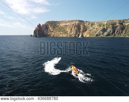 Happy People Are Going To Swim On An Air Mattress Behind A Jet Ski. Tourists Ride The Inflatable Wat