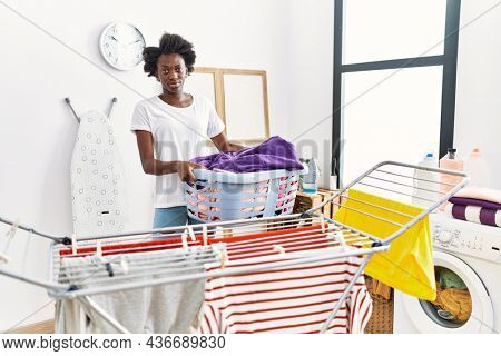 African young woman doing laundry at clothesline skeptic and nervous, frowning upset because of problem. negative person.