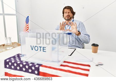 Handsome middle age man sitting at voting stand disgusted expression, displeased and fearful doing disgust face because aversion reaction. with hands raised