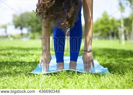 Young Woman Doing Yoga Exercise On Green Grass