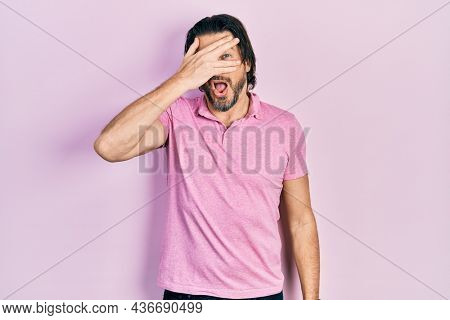 Middle age caucasian man wearing casual white t shirt peeking in shock covering face and eyes with hand, looking through fingers with embarrassed expression.