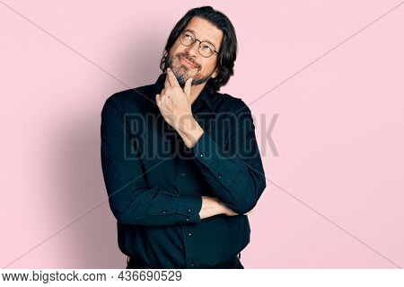 Middle age caucasian man wearing casual clothes and glasses with hand on chin thinking about question, pensive expression. smiling with thoughtful face. doubt concept.