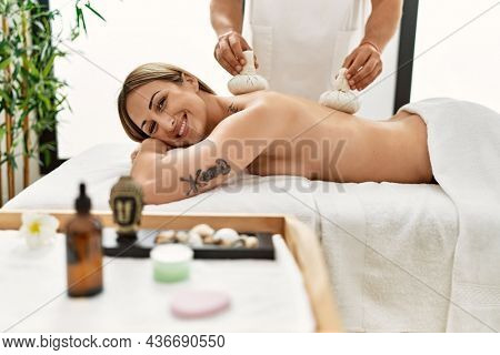 Young caucasian woman at physiotherapy clinic getting muscle massage by professional therapist. Physiotherapist man doing tea bag treatment to client