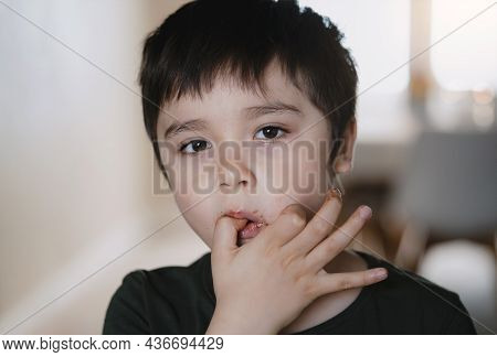 Head Shot Happy Young Kid Looking At Camera While Sucking Thumb After Eating Chocolate Cake, Close U