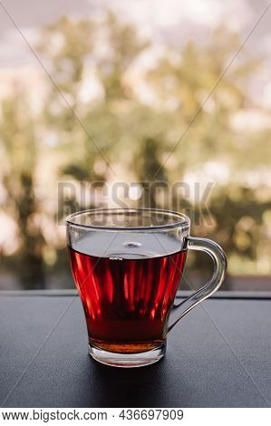 A Cup Of Fragrant Tea Stands Near The Window. Transparent Mug With A Drink