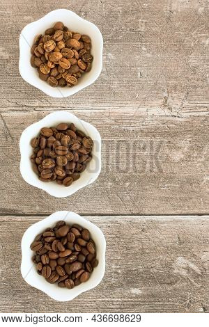 Light Roast, Medium Roast And Dark Roast Speciality Arabica Beans In White Bowls Over Brown Weathere