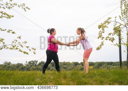 Wide Shot Of Professional Fitness Female Trainer Giving Personal Training To Overweight Young Woman