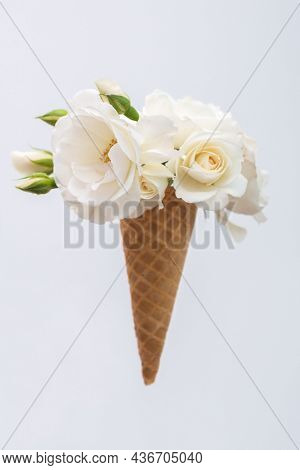 Ice cream waffle cone with a bouquet of summer flowers white roses. Diet and thinking outside the box design concept