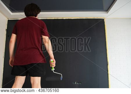 Roller Wall Painting. Man standing near black wall and holding roller, back view. Worker ready to paint, home renivation. Painter at work. Home renovation