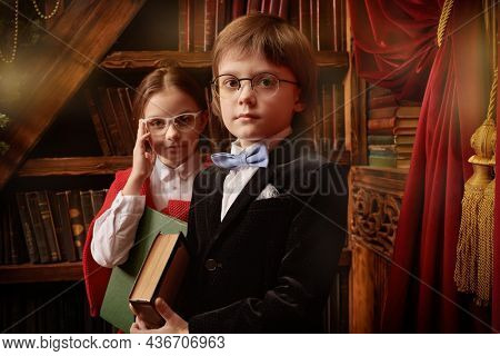 Pair of schoolchildren dressed in fashionable school clothes pose in a splended vintage interior by a bookcase with books in their hands. Kid's school fashion.