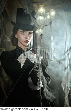 Curious young noblewoman in a 19th century dress wanders around an old vintage castle enveloped in mysterious white haze.