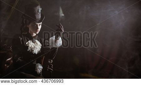 History and Fashion of the late 19th - early 20th century. Confident young lady in a black dress and hat sits in a dark vintage room being about to snap her fingers. Copy space.
