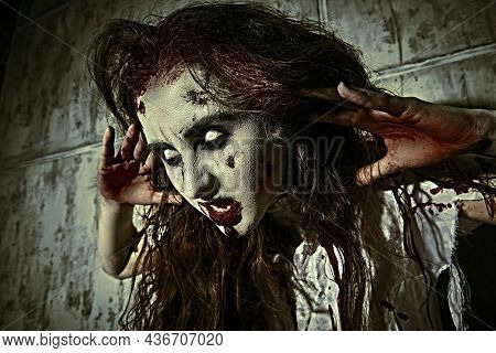 Portrait of a creepy zombie woman with faded eyes and shaggy hair standing in a bloody nightie against the background of a concrete wall. Obsessed woman. Horror, thriller. Halloween.