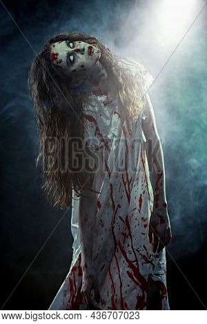 Obsessed woman with faded eyes and shaggy black hair standing in a bloody nightie in a dark room and looking at a beam of light descending from above. Zombie woman. Horror, thriller. Halloween.