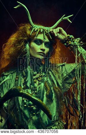 Portrait of a shaman woman in ritual clothes and deer antlers headdress posing in the dark background lit by fire behind her. Ethnic traditions. Paganism. Halloween.