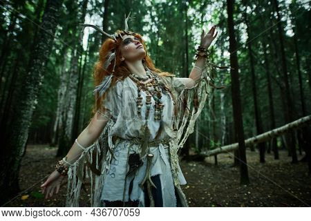 Portrait of a shaman woman in ethnic dress and deer antlers headdress performing a mysterious ritual dance in a forest. Fairy forest witch. Fantasy. Halloween.