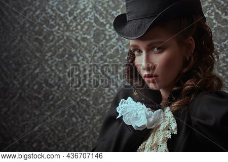 Portrait of a refined elegant lady in a 19th century suit posing on a vintage background with fear on her face. 19th century fashion and beauty. Copy space.