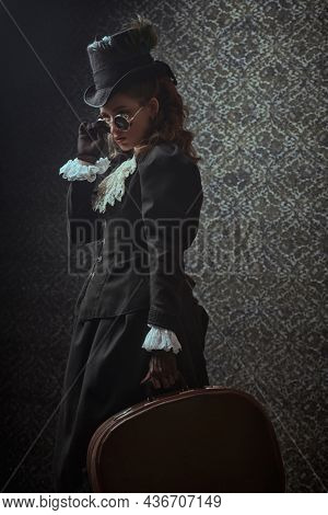 Portrait of an elegant woman in traditional 19th century clothes and stylish sunglasses posing on a vintage background with a traveling bag in her hand. Style of the late 19th - early 20th century.