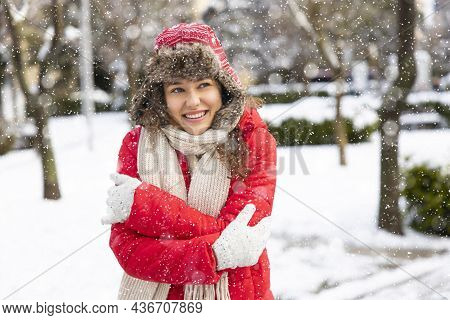 Portrait Of Young Beautiful Woman With In Red Winter Clothes And Strong Snowing Winter Day In The Ci