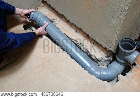 Plumber assembling pvc sewage pipes