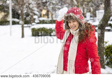 Young Smiling Woman Playing With A Snowball Winter Snowy Day In The City