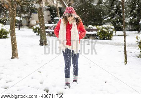 Young Woman In Red Coat Walking In The City On A Snowy Winter Day