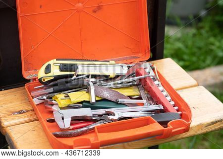 Orange Plastic Box Containing Professional Toolkit For Handyman Lies On Wooden Bench Against Blurred