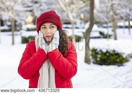 Young Woman Portrait On A Snowy Winter Day. Overcast And Cold Weather. She Is Heating Her Face With